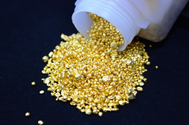 Imagem do conceito desfoque um ao outro no centro e ao redor da imagem borrada. de pepitas de ouro derramadas em tecido de veludo