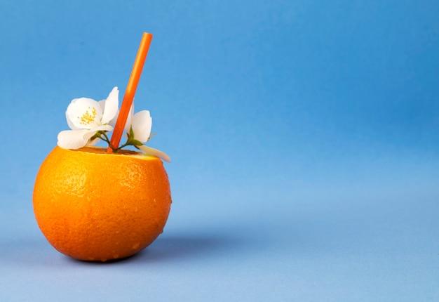 Imagem do conceito do verão de uma laranja fresca em um fundo azul e copyspace para o texto