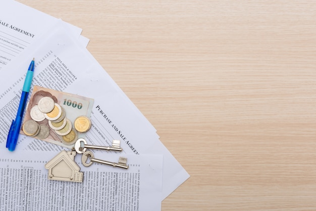 Imagem do contrato de locação residencial com dinheiro e chaves.