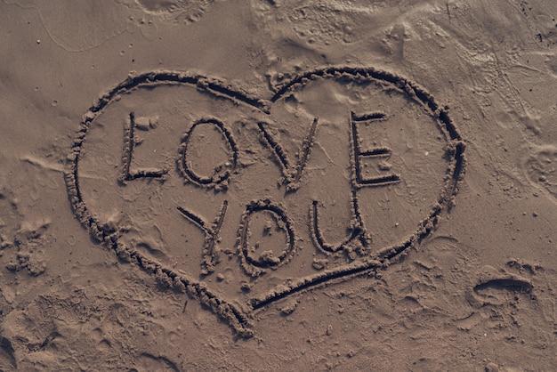 Imagem do coração com 'te amo' assinar na areia