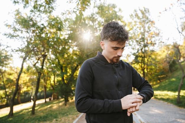 Imagem do corredor de homem de aptidão de esportes jovem bonito ao ar livre no parque, olhando para o relógio do relógio.