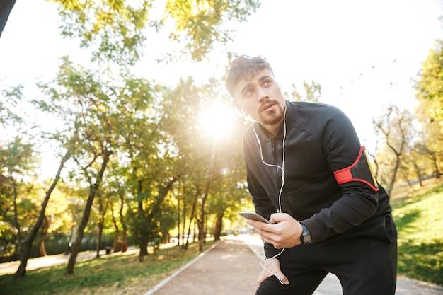 Imagem do corredor de homem de aptidão de esportes jovem bonito ao ar livre no parque, ouvindo música com fones de ouvido, usando telefone celular.