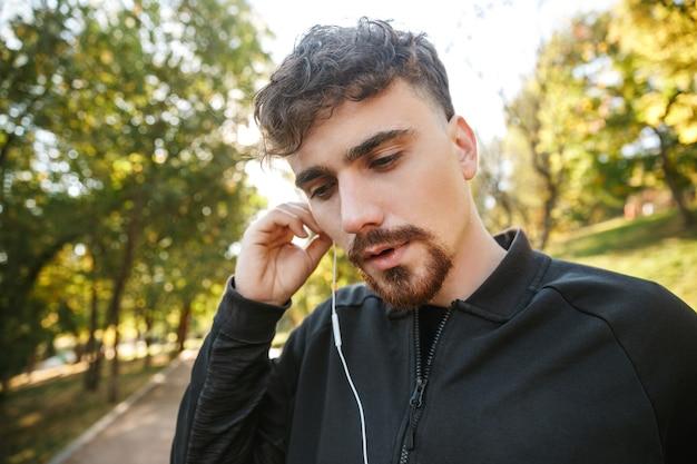 Imagem do corredor de homem de aptidão de esportes jovem bonito ao ar livre no parque ouvindo música com fones de ouvido.
