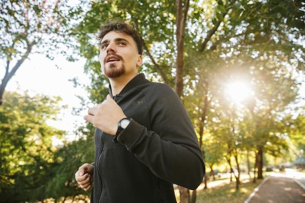 Imagem do corredor de homem de aptidão de esportes jovem bonito ao ar livre no parque.