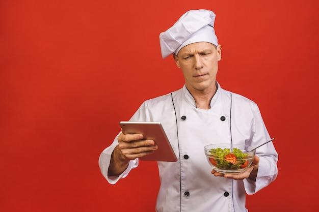 Imagem do cozinheiro novo feliz do chefe sênior na posição uniforme isolada sobre o fundo vermelho da parede, guardando a salada e o tablet pc.