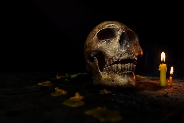 Imagem do crânio na escuridão com luz da vela. conceito de halloween
