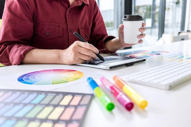 Imagem do desenhista gráfico criativo fêmea que trabalha na seleção de cor e que tira na tabuleta de gráficos