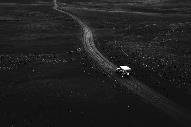 Imagem do drone de um suzuki jimny dirigindo em uma estrada de terra