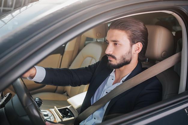 Imagem do empresário agradável e confiante, sentado no carro de luxo. ele olha para a frente. poses de homem. ele tem o cinto de segurança trancado e oingando por todo o corpo.