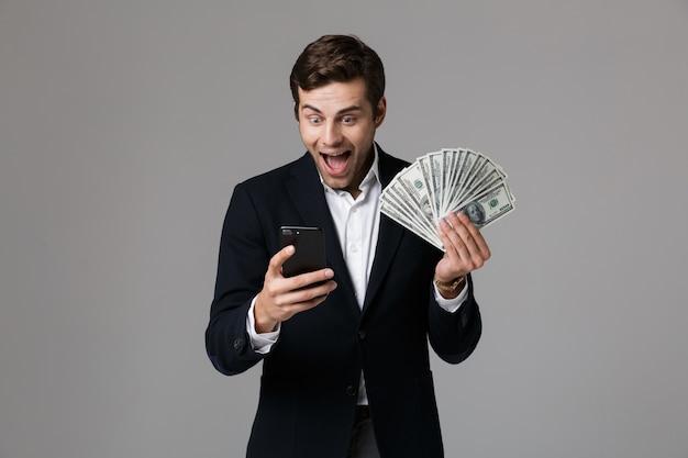 Imagem do empresário caucasiano dos anos 30 de terno segurando um leque de dinheiro e smartphone, isolado sobre uma parede cinza