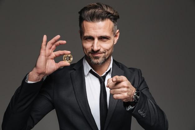 Imagem do empresário masculino feliz no terno e gravata, segurando a moeda criptográfica e apontando o dedo na câmera, isolada sobre a parede cinza escura