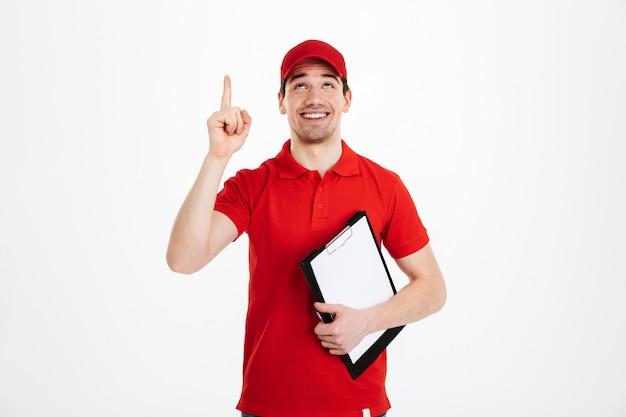 Imagem do entregador otimista de camiseta vermelha e boné sorrindo e apontando o dedo no texto ou produto copyspace enquanto segura a área de transferência, isolada sobre o espaço em branco