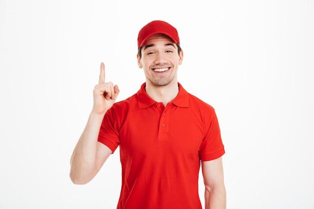 Imagem do entregador otimista de camiseta vermelha e boné sorrindo e apontando o dedo para cima no texto ou produto copyspace, isolado sobre o espaço em branco