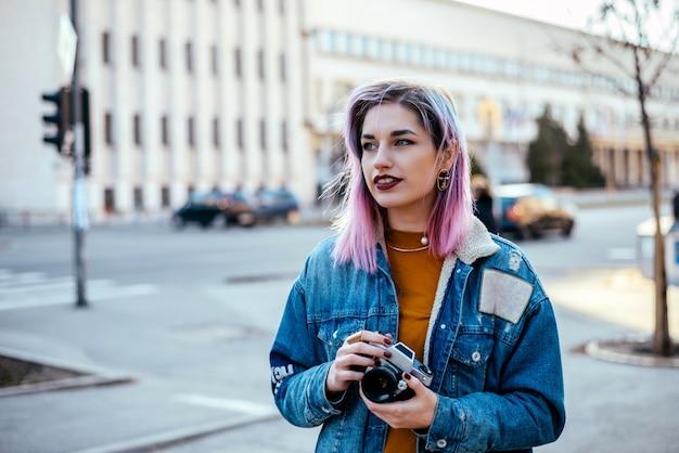 Imagem do estudante fêmea ou do fotógrafo bonito com cabelo cor-de-rosa na rua da cidade.
