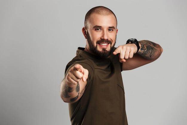Imagem do homem alegre forte com tatuagem nas mãos, apontando os dedos perto, isolado sobre a parede cinza