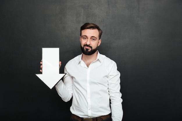 Imagem do homem chateado pessimista 30s segurando o ponteiro de seta do discurso em branco direcionando para baixo sobre o espaço da cópia da parede cinza escuro