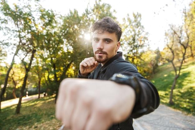 Imagem do homem de aptidão de esportes jovem bonito ao ar livre no parque fazer exercícios de boxe.