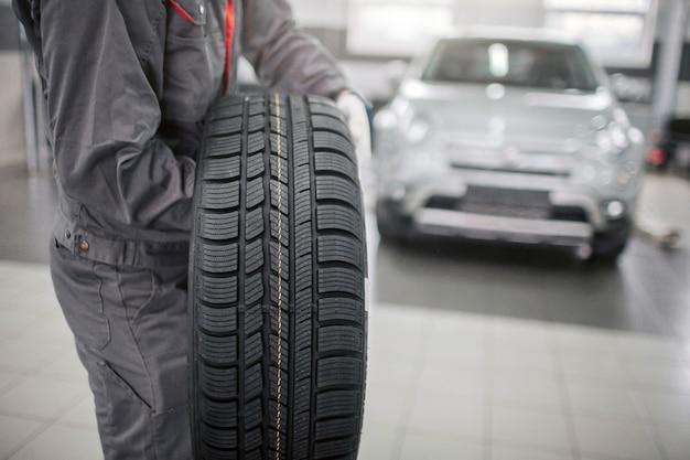 Imagem do homem de uniforme cinza fica e segura a roda do carro com as duas mãos. é pesado. carro branco está atrás dele.