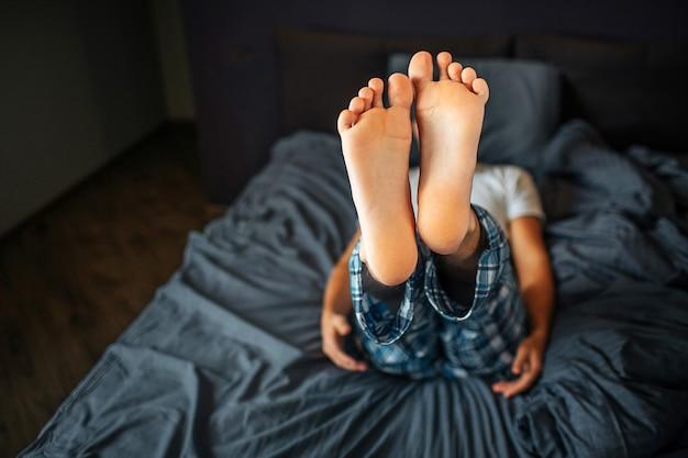 Imagem do homem deitado na cama e mostrando os dois pés na câmera. a pele é saudável e limpa. o homem está no quarto de dormir. ele veste pijama.
