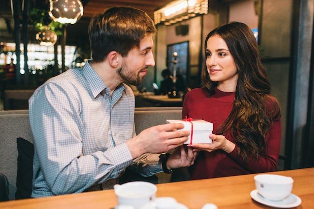 Imagem do homem que dá um presente a uma mulher. eles estão olhando um para o outro e sorrindo um pouco. eles estão sentados no restaurante.