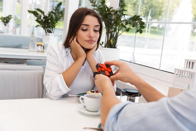 Imagem do incrível jovem casal apaixonado, sentado no café. homem dá um presente para a namorada.