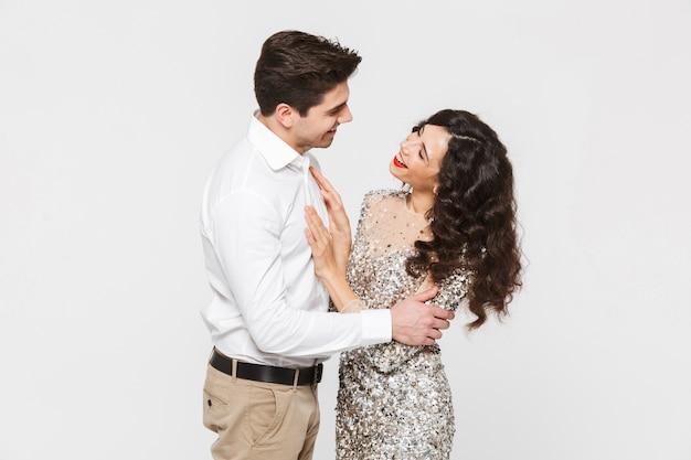 Imagem do jovem casal amoroso feliz em pé isolado sobre os abraços brancos.