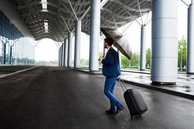 Imagem do jovem empresário segurando a mala e o guarda-chuva no terminal chuvoso