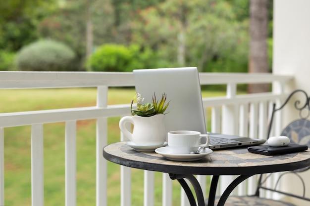 Imagem do laptop com a xícara de café e planta na mesa na varanda com vista para o jardim.