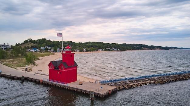 Imagem do lindo farol vermelho com bandeira americana no cais à beira do lago com propriedades na praia