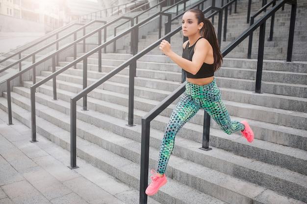 Imagem do modelo de execução rápida. ela faz isso nos degraus. jovem mulher se ajuda com as mãos. ela corre o mais rápido que pode. jovem mulher posa na câmera desta maneira.
