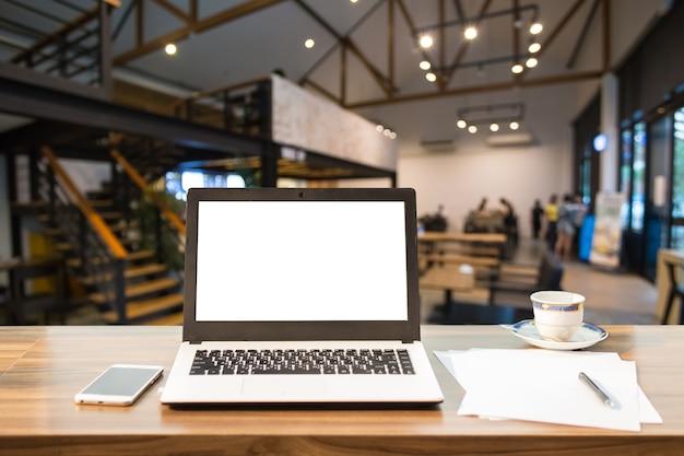 Imagem do modelo do portátil com a tela branca vazia na tabela de madeira na cafetaria.