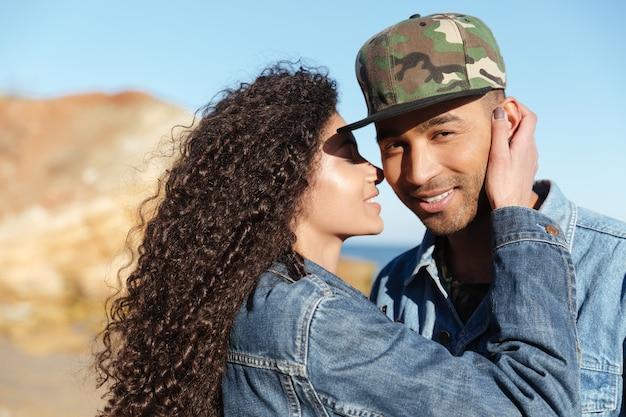 Imagem do par loving africano feliz que anda ao ar livre na praia. mulher beijando uma bochecha de menino.