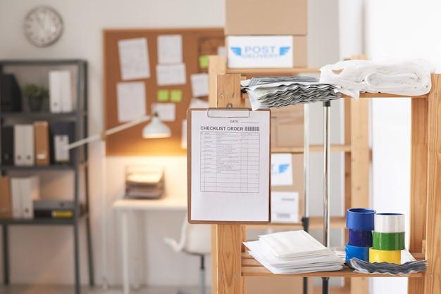 Imagem do pedido da lista de verificação na prancheta pendurada na parede de vidro de um escritório moderno