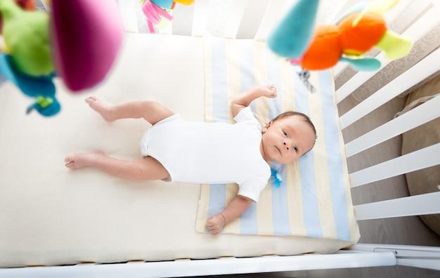 Imagem do ponto de vista superior de um bebê deitado em um berço branco em um dia de sol