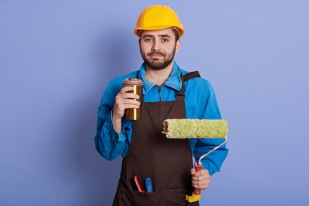 Imagem do reparador agradável de trabalho duro que guarda a caneca thermo com bebida quente e rolo para a pintura de parede, tendo a pausa para o café, vestindo uniforme com equipamento, tendo o descanso, apreciando a hora do almoço.