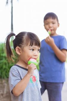 Imagem do retrato de um bebê de 3-4 anos. irmãos de crianças asiáticas felizes comendo e mordendo um sorvete vermelho. temporada de verão, sentimento delicioso, rosto desleixado de infância.