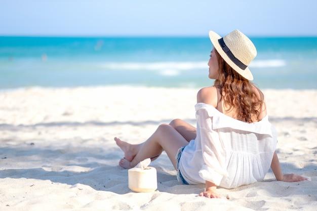 Imagem do retrato de uma linda mulher asiática, sentando-se e bebendo suco de coco na praia