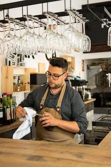Imagem do vidro de vinho da limpeza do empregado de mesa em um bar. profissão, conceito de estilo de vida, trabalho.