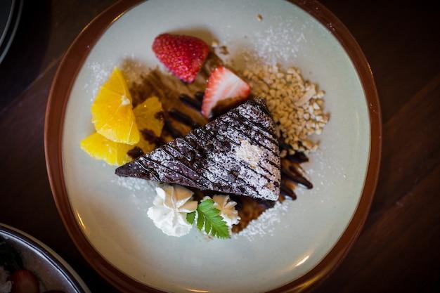 Imagem dos brownies de chocolate amargo caseiros e morango e laranja fresca