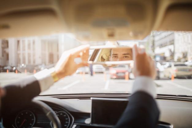 Imagem dos olhos do homem olhando direto do espelho raro. ele segura com as duas mãos. cara senta no carro, ele tem terno em si mesmo.