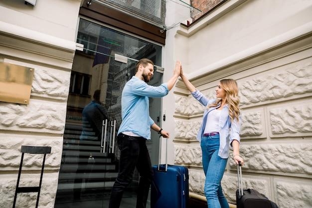 Imagem dos pares novos que sorriem e que dão cinco ao entrar no hotel. casal feliz com malas em pé perto do antigo edifício da cidade