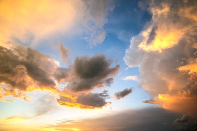 Imagem dramática da paisagem do sol com nuvens inchadas iluminadas pelo pôr do sol laranja e pelo céu azul.