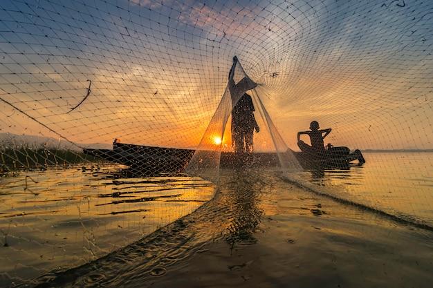 Imagem é silhueta. os pescadores lançam um peixe de manhã cedo com barcos de madeira.