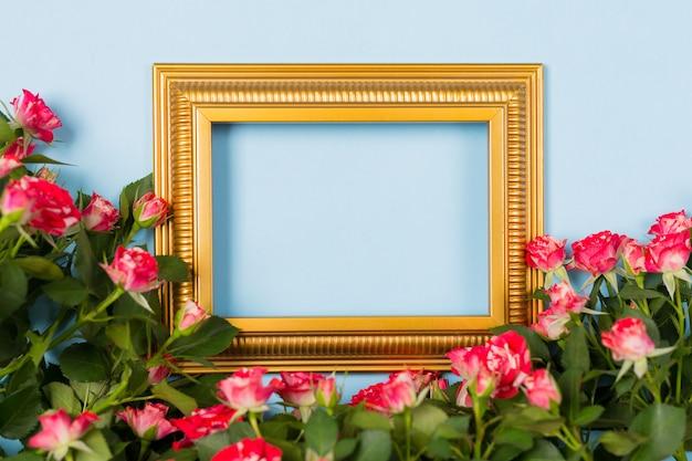 Imagem em branco vazia de moldura dourada cercado spray rosas vermelhas sobre fundo azul claro