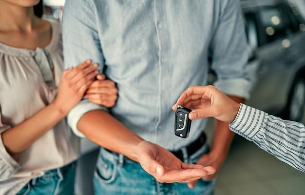 Imagem em close de casal que comprou um carro na concessionária e recebe as chaves do gerente.