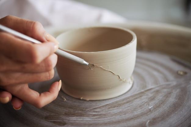 Imagem em close de ceramista removendo quantidades controladas de argila de uma panela de barro derrubada com uma fita.