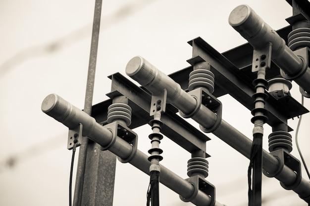 Imagem em escala de cinza com foco seletivo de linhas de alta tensão, conexões e transformador