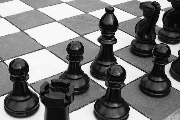 Imagem em escala de cinza de alto ângulo das grandes peças de xadrez no tabuleiro