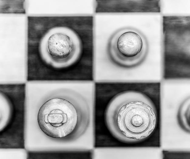 Imagem em escala de cinza de peças de xadrez em um tabuleiro de xadrez
