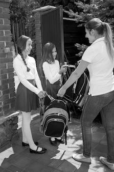 Imagem em preto e branco da mãe dando mochilas para as filhas indo para a escola pela manhã